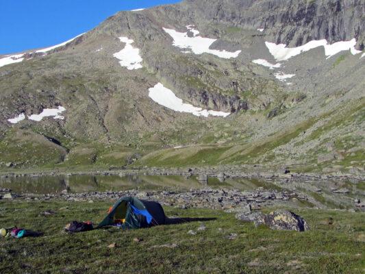 Litet tält på barmark nedanför stor snöklädd fjälltopp.