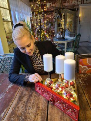 Sara sitter vid bordet vid sin ljusstake gjord av en trekantig röd låda, gamla vinglas och julgranskulor.
